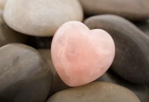 Rose quartz heart on pebbles