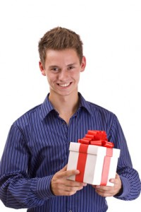 young attractive man with a wrapped gift box for you